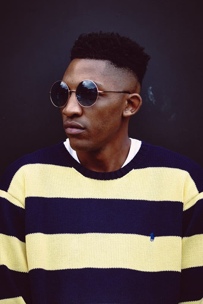 man in blue and white striped crew neck shirt wearing black sunglasses